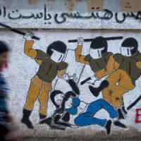 Overpowering: A woman walks past a mural in Cairo's Tahrir Square last September that was inspired by a widely circulated photograph of Egyptian police brutally beating and stripping a veiled female protester. | AP