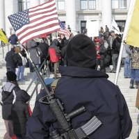 Strapped: A firearms rights advocate carries an AR-15 with a U.S. flag in the barrel outside the Utah state Capitol in Salt Lake City during a Gun Appreciation Day Rally in January. | AP