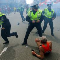 City under attack: A man lies on the ground as police officers react to a second explosion at the finish line of the Boston Marathon in the city Monday. | AP