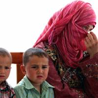 Temporary home: A newly arrived Syrian refugee woman covers her face as she sits on a bench with her children at the Mrajeeb al-Fhood refugee camp in Zarqa, Jordan, on Monday. | AP