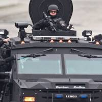 Heavily armed police patrol a neighborhood in the suburb while riding on an armored Humvee the same day. | AP