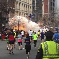 Crossing the line: Runners make their way to the finish line of the Boston Marathon as a bomb explodes on April 15. Two explosions, about 10 seconds apart, ripped through the crowd, killing three and seriously wounding scores. | REUTERS/KYODO