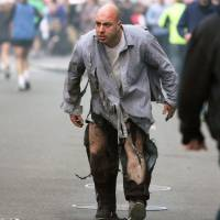 A man, whose clothes were shredded in the bombing, stumbles away from the scene of the two explosions on April 15. | AP