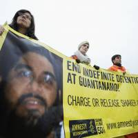 Still behind bars: Activists hold a banner with a photo of Guantanamo detainee Shaker Aamer, at a rally in Washington on Jan. 11. Captured by U.S. forces in Afghanistan in 2001, Aamer has been imprisoned for the past 12 years without being charged. | AP