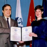 Two faces: In 1997, CIA Director George Tenet awards Ana Montes the Certificate of Distinction, the third-highest national-level intelligence honor. While Montes was excelling at her U.S. government job, she also was spying for Cuba. At right, her FBI booking photo on the day of her arrest, Sept. 21, 2001. | COURTESY OF DEFENSE INTELLIGENCE AGENCY