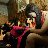 Perilous profession: A policeman watches over a group of girls, suspected of being sex workers, during an inspection of a nightclub in Beijing. | AP
