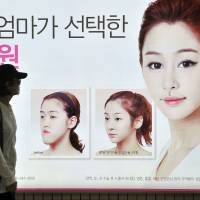 Jaw-dropping: A woman walks past a billboard advertising double-jaw surgery at a Seoul subway station on Wednesday. | AFP-JIJI