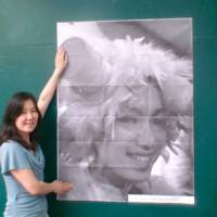Poster women: Aya Suzuki puts up a poster of Naho Iguchi on a wall in a Meguro-ku children's playground. Both women are volunteers, organizing free public lecture events through TEDxTokyo. | COURTESY OF 'INSIDE OUT,' TOKYO