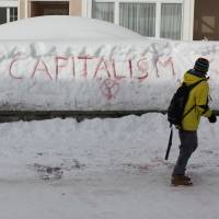 Symbol: A man looks at graffiti on snow in Davos, Switzerland, ahead of the World Economic Forum in January 2012. | BLOOMBERG