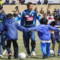 Team spirit: Veteran soccer star Kazuyoshi Miura takes to the pitch with young evacuees in Morioka, Iwate Prefecture. | KYODO PHOTO