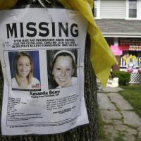 Yellow ribbon: A missing poster still rests on a tree outside the Cleveland home of Amanda Berry after she was found on May 6. Berry and two other women had been held captive in a house nearby for a decade. The advent of the early-warning system Amber Alert now makes it easier to inform the public when a child goes missing. | AP