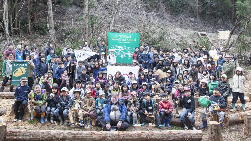 All smiles: Volunteers from Higashi Matsushima pose with he they call 'Uncle Nic' below the overgrown slope up which the Tree Dragon now rears.