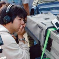 Quiet on the set: Director Yuya Ishii examines a shot through a monitor on the set of his latest film, 'Azemichi no Dandy.' | (C) 2011 'AZEMICHI NO DANDY' SEISAKU IINKAI