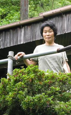 Looking back: Akiko Karitani outside her old home in the now nearly abandoned hamlet of Akagura. | WINIFRED BIRD