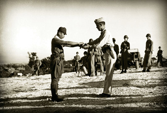 Unbowed:  Renegade Capt. Sakae Oba surrenders his sword to a U.S. officer on Dec. 1, 1945.   PHOTO COURTESY OF GORDON MARCIANO