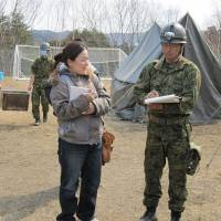 Futaba Kaiharazuka speaks with a Self-Defense Force officer during her group's relief efforts in Yamada, Iwate Prefecture, following the March 11 earthquake and tsunami. | COURTESY OF CARE INTERNATIONAL JAPAN