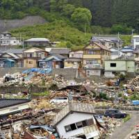 Life and death: After major tsunamis in 1896 and 1933, many houses in Toni, Iwate Prefecture, were relocated from low-lying valleys to 'reconstruction zones' on higher land (background, above). But tragically, many others were built in their place (foreground). | YOSHIAKI MIURA PHOTO