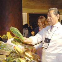 Let's get cooking: Chef Yoshihiro Murata of Kikunoi examines vegetables produced in Tohoku during the May 31 event held at a hotel in Tokyo.   MELINDA JOE PHOTOS