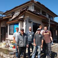 Zenetsu Nishiyama (second from left) stands in front of his tsunami-damaged home in Ofunato, Miyagi Prefecture, along with members of All Hands volunteer group. | JON MITCHELL PHOTOS