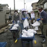 Mucking in: Volunteers from the Shangri-La Hotel Tokyo shift bags of sludge they dug out of drainage gutters in Ishinomaki, Miyagi Prefecture, on Tuesday. | TOMOKO OTAKE PHOTOS