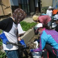 Hard labor: Volunteers from the Shangri-La Hotel Tokyo remove foul-smelling sludge that has been clogging the drainage gutters in a residential part of Ishinomaki, Miyagi Prefecture, since the Great Eastern Japan Earthquake and tsunami struck on March 11.
