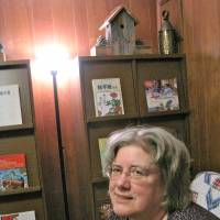 Deborah Davidson sits at her home in Sapporo, surrounded by some of her published works and favorite books. Below: An etegami featuring the image of catfish is one of the series that Davidson posted on her blog following the March 11 earthquake and tsunami. | KRIS KOSAKA, COURTESY OF DEBORAH DAVIDSON