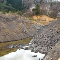 Paying the price: A Nagano Prefecture hill dug away to refill huge holes left by gravel extraction from lowland site.   WINIFRED BIRD