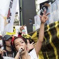 Fight the power: Hip-hop artist Rumi performs during an antinuclear power protest in Tokyo's Koenji neighborhood on April 10. | MASABUMI KIMURA