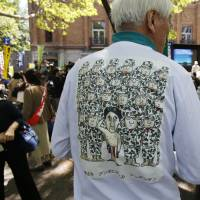 A protester shows off a T-shirt depicting him in Stars and Stripes underwear saluting Self-Defense Forces personnel at Friday's rally in Tokyo.   AP