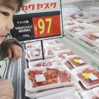 Target market: A young customer checks out U.S. beef products at a supermarket in Kita  Ward, Tokyo, after they went on sale in February because import restrictions were eased. | KYODO