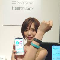 Wrist strong: A model wears a Fitbit flex wristband that can send health and fitness information to a Softbank smartphone.   KAZUAKI NAGATA