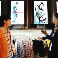 Showtime: Salesclerk Shohei Sugiyama (right) shows a customer how to turn on a video by picking up a hanger with an embedded sensor at the Vanquish store in Shibuya Ward, Tokyo, on April 19. | YOSHIAKI MIURA