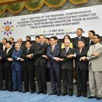 Hand in hand: Representatives of 16 Asia-Pacific economies pose for a photo Thursday in Brunei as they kick off a meeting on free trade. | KYODO