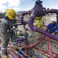 No wrenching changes:  Workers tend to a well head during a hydraulic fracturing operation at an Encana Oil & Gas facility outside Rifle, western Colorado, in March. | AP