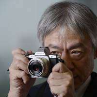 Snap happy: Olympus CEO Hiroyuki Sasa takes a photo with one of the company's cameras in Tokyo on Monday. | BLOOMBERG
