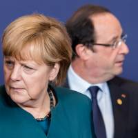 Taxing business: German Chancellor Angela Merkel and French President Francois Hollande walk away after a group photo was taken during an EU summit in Brussels on Wednesday. | AP