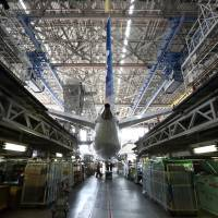 More power: Engineers work to install a redesigned battery into a Boeing Co. 787 Dreamliner owned by All Nippon Airways Co. in a hangar at Haneda airport in Tokyo on April 28. | BLOOMBERG