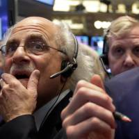Second thoughts: Trader Peter Tuchman works the floor of the New York Stock Exchange on Thursday. On Wall Street, traders are  worried about how committed the Federal Reserve is to maintaining its unorthodox bond-buying program. | AP
