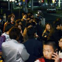 Residents watch the tense 13-hour standoff. | KYODO