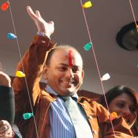 Free at last: Govinda Prasad Mainali waves from his Katmandu home on Nov. 7 after learning of his exoneration. | KYODO