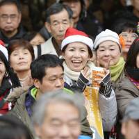 Campaign spirit: Voters listen to a politician's speech in front of JR Shinjuku Station on Tuesday. | KYODO
