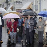 Residents in Aizuwakamatsu, Fukushima Prefecture, gather for a campaign speech outside their temporary housing units the same day. | KYODO