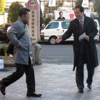 Shifting tides: Liberal Democratic Party candidate Masatada Tsuchiya greets supporters Thursday at Kichijoji Station in the Tokyo No. 18 district. Below: A man hurries by former Prime Minister Naoto Kan, the district's current Lower House member, during a campaign event Wednesday. | ALBERT SIEGEL, AYAKO MIE