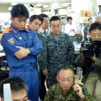 Not a test: Ishigaki Mayor Yoshitaka Nakayama (left) and Self-Defense Forces staff watch a screen of the J-Alert ballistic missile warning system in Ishigaki, Okinawa Prefecture, on  Wednesday. | KYODO