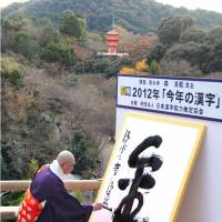 Golden year: Seihan Mori, chief monk of Kiyomizu Temple in Kyoto, writes the kanji for gold on a white screen Wednesday at the temple. The character was chosen by the public as best representing this year.   KYODO