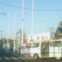 Stumped?: Former Prime Minister Naoto Kan's campaign van sits in an intersection Thursday in the Tokyo suburb of Fuchu after scraping center-divider posts. | KYODO