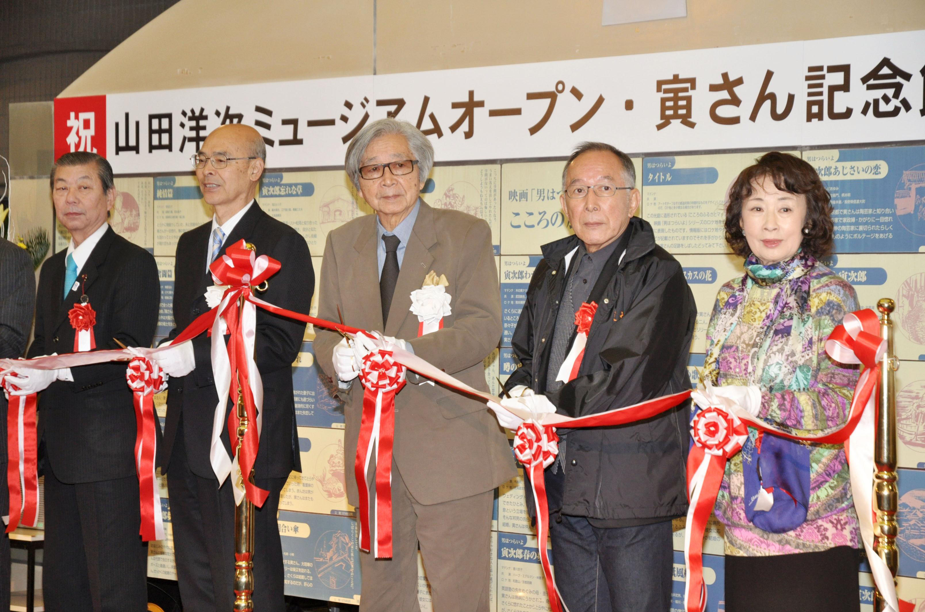 Making the cut: Lauded film director Yoji Yamada (center) takes part in a tape-cutting ceremony Saturday for a new museum dedicated to his works in Katsushika Ward, Tokyo. | KYODO