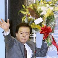 To the victor: Naoki Inose, who won the Tokyo gubernatorial election, waves to supporters Sunday night at his campaign office in Shinjuku Ward. | KYODO