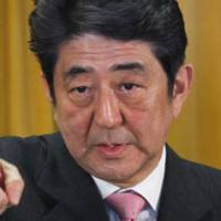 Back in the saddle: Liberal Democratic Party President Shinzo Abe faces reporters Monday at LDP headquarters in Tokyo following the party's big win in Sunday's general election. | AP