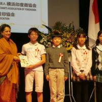 Indian Ambassador Deepa Gopalan Wadhwa presents the manga 'Secrets of India' to Japanese elementary school students at the embassy in Tokyo on Dec. 14. | CHIHO IUCHI
